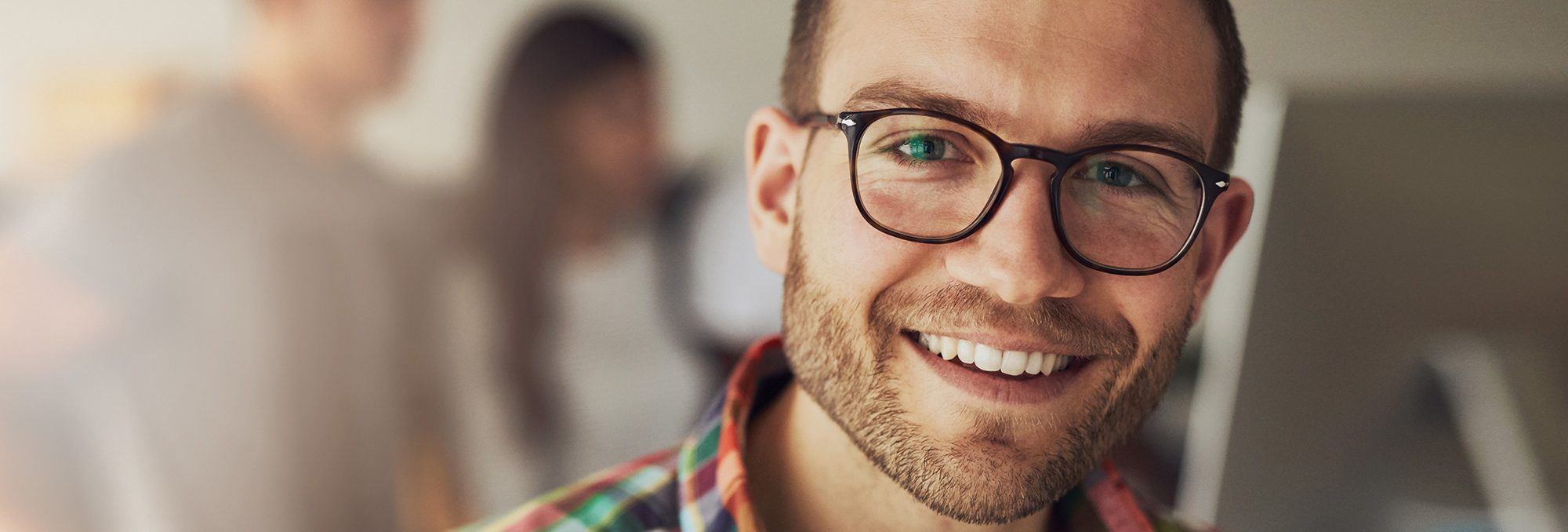 A young man with nice glasses and stubble