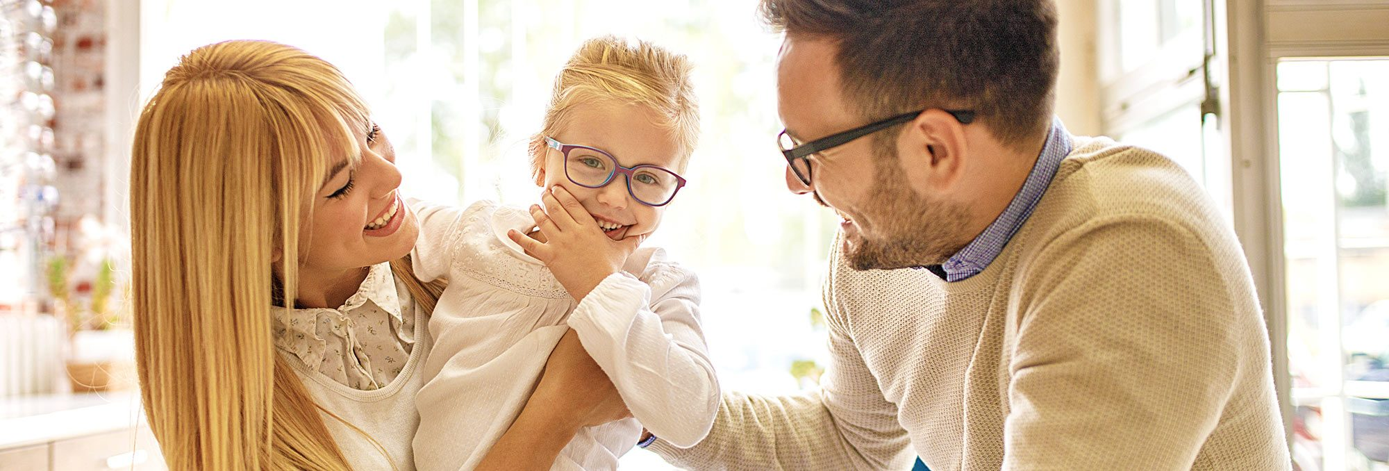 Young family trying on glasses together at optical shop
