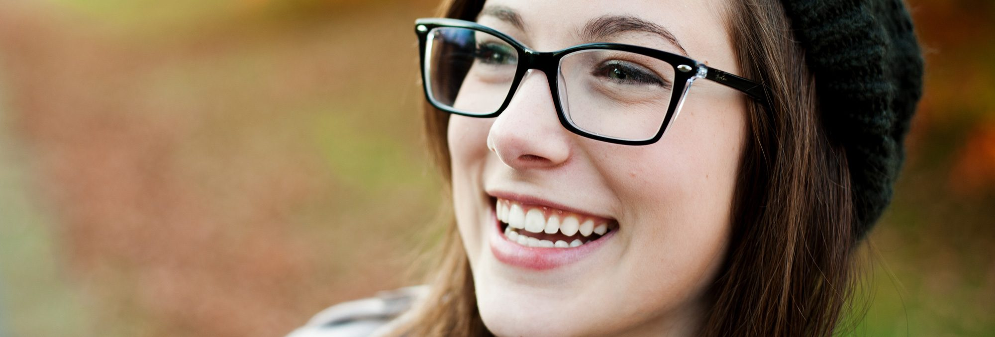 Young woman with beanie and glasses smiling
