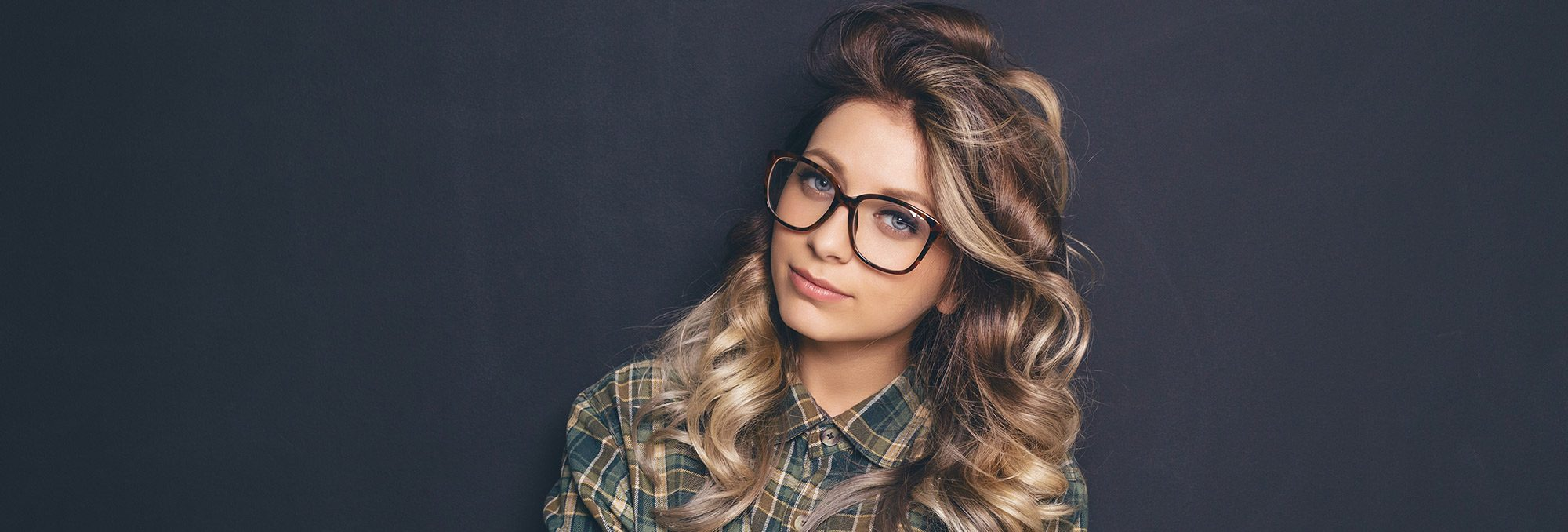 Young woman with plaid shirt and large eyeglasses
